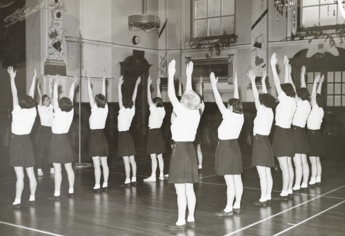 HD/1/443: An exercise class for female patients in the recreation hall, c1950s.