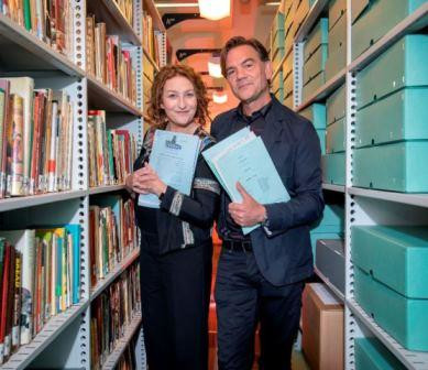 Blythe Duff and John Michie standing side by side between shelves of archive boxes and materials. Each is looking into camera and holding several scripts.
