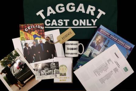Selection of photographs, artefacts, all from television show Taggart, artfully laid on black backdrop.